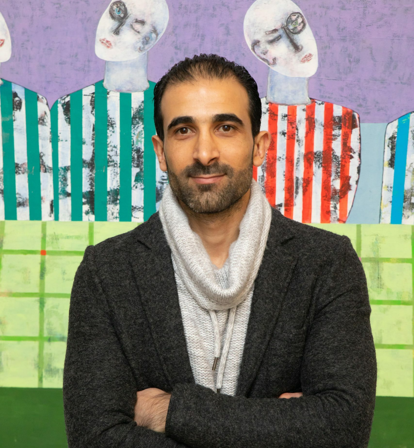 """Rashwan Abdelbaki poses in front of his work, """"Last Supper, First Wall"""""""