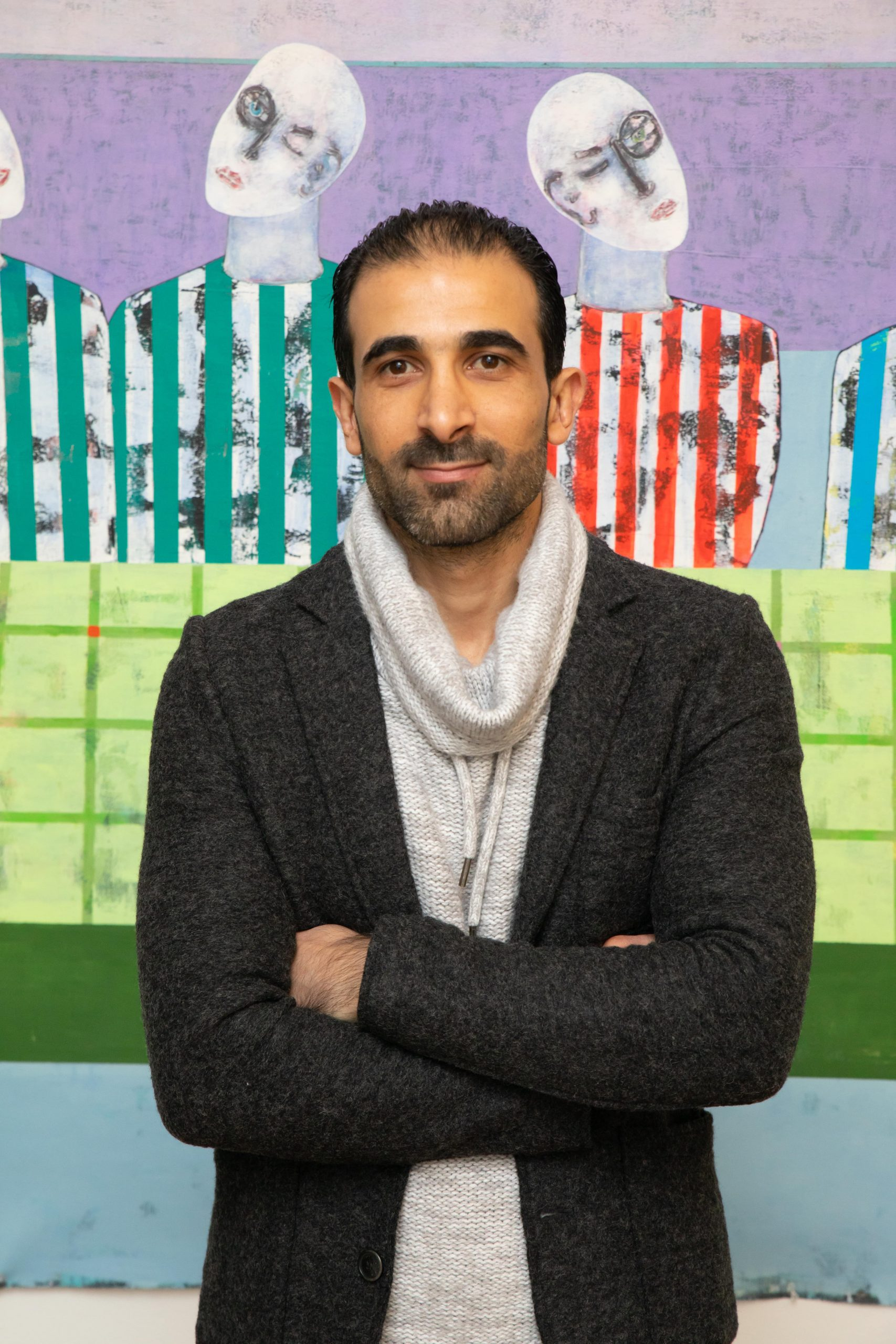 "Rashwan Abdelbaki poses in front of his work, ""Last Supper, First Wall"""