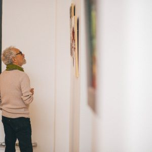 Guest admires artwork at AFI's First Annual Celebration. Westbeth Artists Housing, December 2017. Photography by Joshua Carrigan.