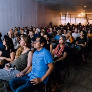 Audience members are captivated by Ash Koosha's performance at Revolutions & Movements Festival. Dupont Underground, September 2018. Photography by Nosrat Tarighi.