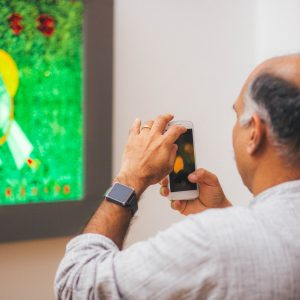 "Guest admires Hadi Nasiri's ""Prayer Hands by Leonardo Da Vinci"" at AFI's First Annual Celebration. Westbeth Artist Housing, December 2017. Photography by Joshua Carrigan."