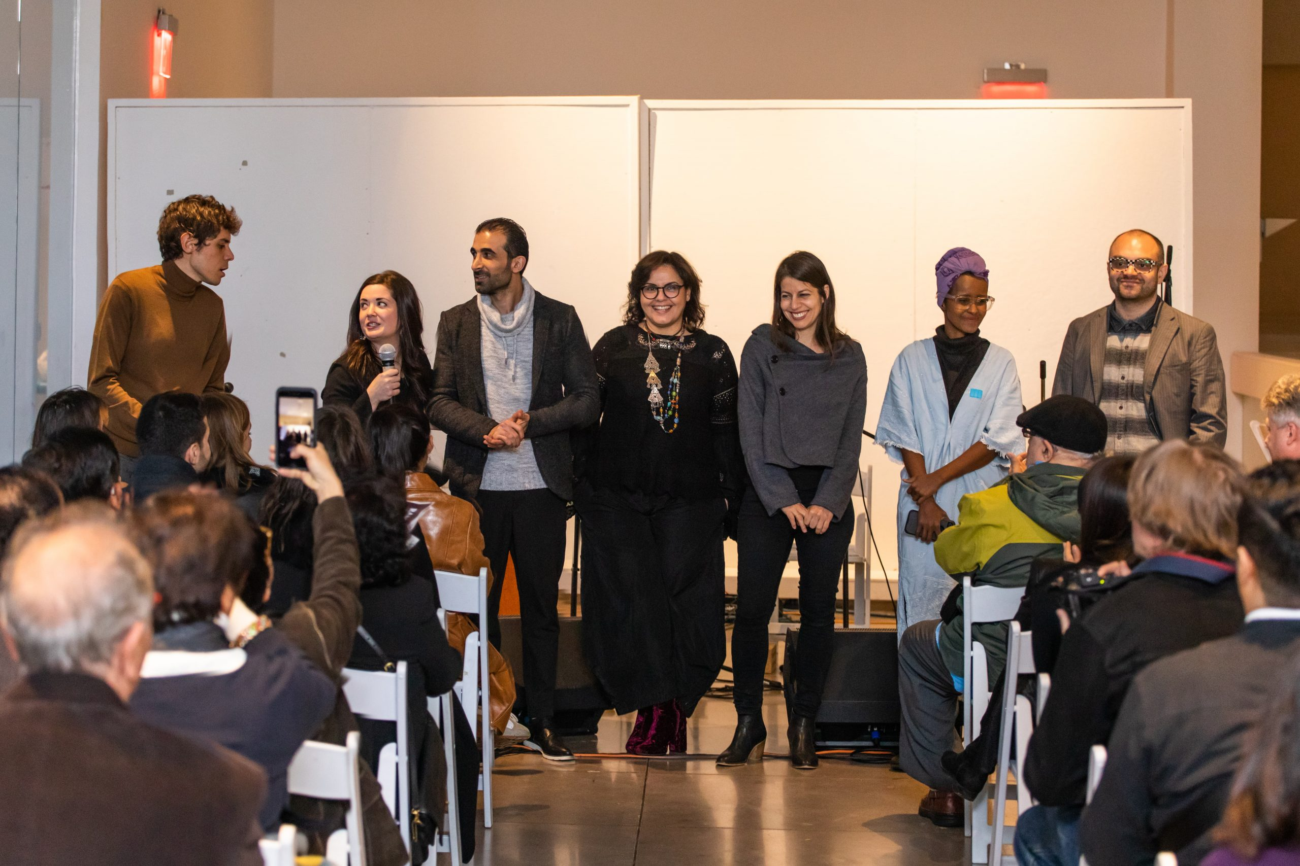 """Exhibiting artists at """"Executive (Dis)Order: Art, Displacement, and the Ban."""" Queens Museum, December 2018. Photography by Michael Wilson."""